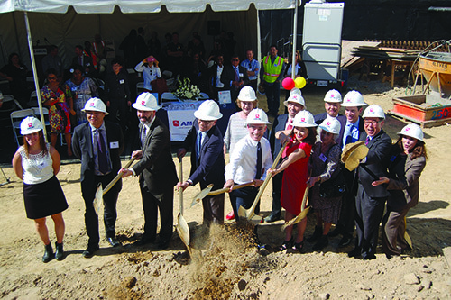 Councilman Mitch O'Farrell, center, breaks ground at the site where 100 affordable units are scheduled to be built. (photo by Gregory Cornfield)