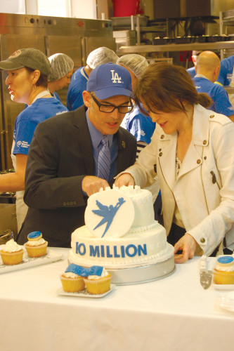 Councilman Mitch O'Farrell and Project Angel Food Founder Marianne Williamson dissect the ceremonial cake. (photo by Gregory Cornfield)