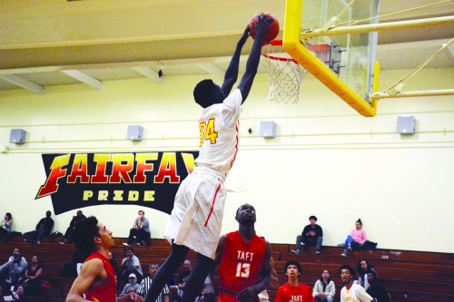 Fairfax High School's Babacar Thiombane jumped high above competitors for a slam dunk during the game against Taft High School on Tuesday. The Fairfax High Lions beat Taft 62-54. (photo by Patricia Sanchez)
