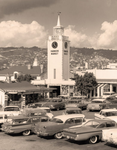 The famed clock tower beckons visitors to the Farmers Market, in the 1970s above, and today, with The Grove shopping center in the background. (photos courtesy of Brett Arena, Farmers Market)