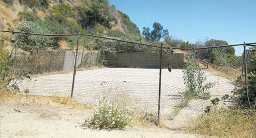 Plans to convert a dilapidated tennis court into a basketball court have been rescinded after public opposition to the project. Some people are calling for the concrete slab to be removed and the site to be returned to a wilderness area. (photo courtesy of FORC)