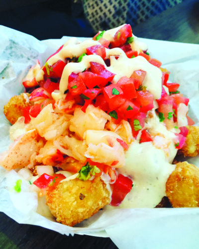 Tater tots are loaded with succulent lobster with creamy cilantro lime sauce and pico de gallo. (photo by Jill Weinlein)
