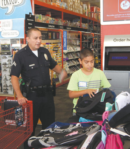 photo by Edwin Folven Officer Jesse Rubacava was paired with Bancroft Middle School student Omar Gonzalez for a school supplies shopping spree organized by the LAPD's Hollywood Division. (photo by Edwin Folven)
