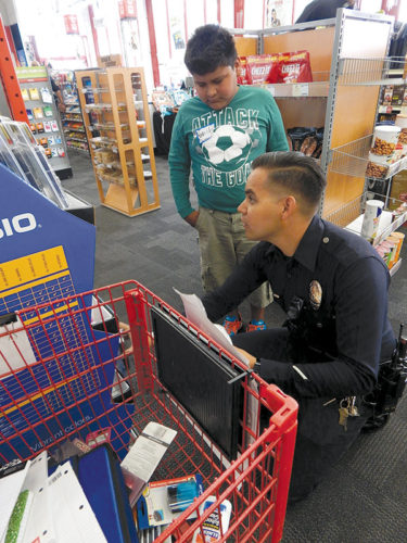 "Officer Gabe Ruiz, of the LAPD's Hollywood Division helped Walter Reed Middle School student Waldo Martinez select back-to-school supplies during ""Shop With a Cop."" (photo by Edwin Folven)"