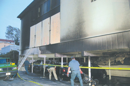 Workers repaired damage at the site of one of the fires attributed to Harry Burkhart in Hollywood. (photo by Edwin Folven)