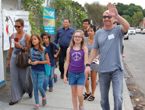 Mark Reavis and his daughter, Samantha greet the morning drop-off volunteers on the first day of classes in 2015 at Hancock Park Elementary School.