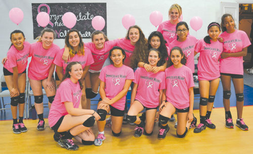 "Immaculate Heart's freshmen/sophomore volleyball team, with coach Alixandra Binney, wore pink shirts and offered small white volleyballs with pink ribbons to their opponents at school's recent ""Breast Cancer Awareness"" volleyball match. (photo courtesy of Callie Webb/Immaculate Heart)"