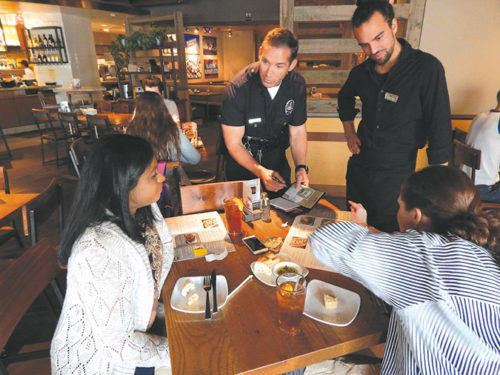 Officer Adam Barnhart was paired with server Trenton Caine during the fundraiser at the California Pizza Kitchen. Customers Jane Salins-Lopez (left) and Anna Ibbotson said they were pleased to participate in the benefit for a good cause. (photo by Edwin Folven)