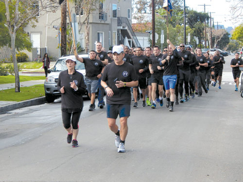 Sandra Navidad, left, the widow of fallen officer Mario Navidad, led officers in a memorial run on Dec. 22 on the 20th anniversary of his death. (photo by Edwin Folven)