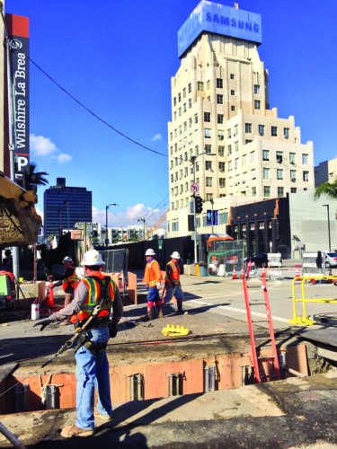 Construction workers with Skanska-Traylor-Shea continue work on the first section of the Metro Purple Line Extension at the intersection of Wilshire Boulevard and Sycamore Avenue. (photo by Gregory Cornfield)