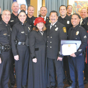 The Wilshire Rotary Club of Los Angeles and the First-In Fire Foundation recently honored a firefighter and police officer from the Wilshire area. Pictured are Capt. Tony Oddo (left), of the LAPD's Wilshire Division; honoree LAFD firefighter Mike Ladue; Capt. Patricia Sandoval, of the Wilshire Division; Lyn McEwen Cohen, president of First-In Fire Foundation; LAFD Capt. Frank Larez; and honoree senior lead officer Hebel Rodriguez, of the Wilshire Division. Ladue's fellow firefighters are pictured in the rear row. (photo courtesy of First-In Fire Foundation)