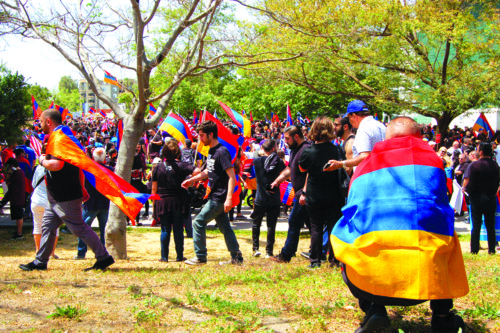 With the Armenian flag draped around him, a man crouches down and observes the scene at Pan Pacific Park on Monday. (photo by Gregory Cornfield)