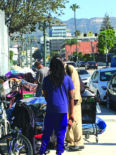 "Homeless individuals and passersby congregate along Cahuenga Boulevard. The county is expected to focus on ""chronically homeless"" people with the first round of ballot measure funds. (photo by Gregory Cornfield)"