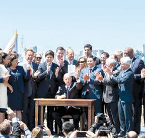 Gov. Jerry Brown (seated) signed a law extending California's cap-and-trade program at a ceremony in SanFrancisco. He was joined by lawmakers from throughout the state. (photo courtesy of Gov. Jerry Brown's Office)