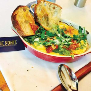 """The """"eggs in Purgatory"""" dish has baked eggs over polenta with a zesty puttanesca sauce.  (photo by Jill Weinlein)"""