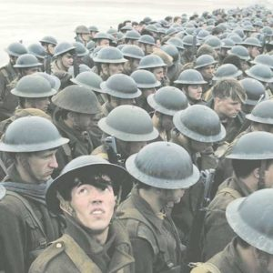"""A British soldier is alarmed by an airstrike while troops wait on the beach in """"Dunkirk,"""" a new film by Christopher Nolan. (photo courtesy of Warner Bros. Pictures)"""