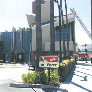 Firefighters climbed on the roof of a fast food restaurant on Western Avenue to extinguish a blaze in the walls and eaves. (photo by Jaclyn Cosgrove)