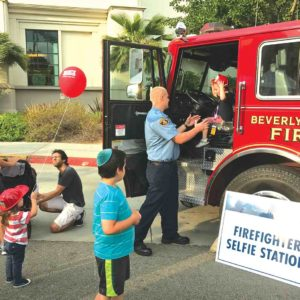 Beverly Hills firefighters gave local children a chance to sit in the driver's seat of a fire truck at the city's National Night Out celebration. (photo by Luke Harold)