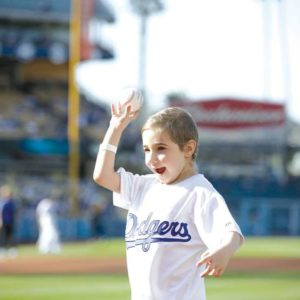 Six-year-old Elysa Shapiro was delighted to toss the ball over home plate at Dodger Stadium. (photo courtesy of Cedars-Sinai Medical Center)