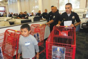 """Hollywood Division Officer Scott Gardner partnered with second-grader Bryan Velazquez during """"Shop With a Cop"""" at Staples on Aug. 14. (photo by Edwin Folven)"""