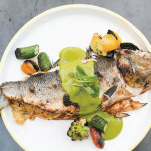 The charcoal-fired whole branzino is topped with a very flavorful green mint aji sauce. (photo courtesy of Rosaliné)