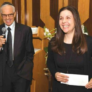 Jenny Zacuto, right, did not know she had been selected to receive the annual prize until her name was called in front of faculty and students by Richard Sandler, left, during an assembly on Tuesday. (photo courtesy of the Milken Family Foundation)