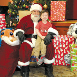 Santa previously welcomed Ian de Mendoza, brother of Cathedral Chapel School fifth-grader Beltran,   and eighth-grader Hugo. (photo courtesy of  Lifetouch Photography)