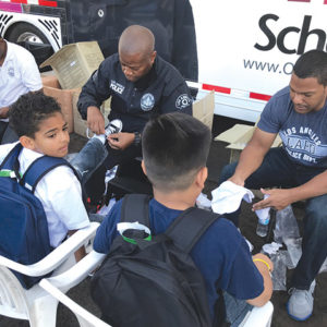 "LAPD Community Service Corporals Eric Desmore and Kirk Madison fit LAUSD students with new shoes at Universal's ""Day of Giving."" (photo by Jill Weinlein)"