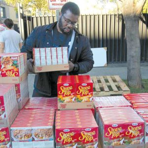 """Preston """"Dozie"""" Itie organized boxes of food to be distributed to people in need at Big Sunday's annual Thanksgiving giveaway. (photo by Edwin Folven)"""