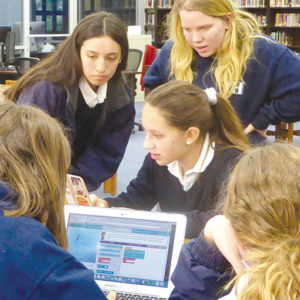 Seniors Cristina Montoya (left) and Theadora Williams helped freshman Hallie Simic (seated, center) during Immaculate Heart High School's Hour of Code event. (photo courtesy of Callie Webb/Immaculate Heart High School)