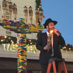 Rabbi Chaim Fischer, of Chabad of the Miracle Mile, lights a LEGO menorah each year during a Hanukkah celebration at the Original Farmers Market. (photo courtesy of Chabad of the Miracle Mile)