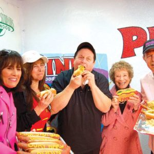 """Pink's Hot Dogs dedicated the new Burt (Robin) Ward Hot Dog on Tuesday in honor of the actor who starred as Robin in the 1960s TV show """"Batman."""" Ward enjoyed the new menu item and was joined by Gloria Pink (left), his wife Tracy Ward, Beverly Pink and Richard Pink. (photo by Edwin Folven)"""