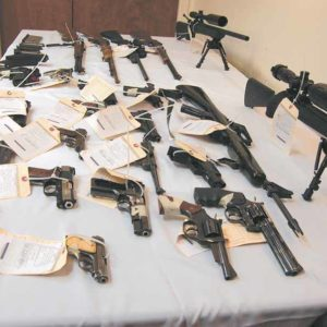Authorities displayed numerous firearms confiscated from a defendant prohibited from possessing them to illustrate how difficult it can be to address illegal guns. (photo by Edwin Folven)