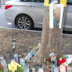 Flowers, candles and photographs were left in front of an apartment building in which two people died  in early March.  (photo by Edwin Folven)