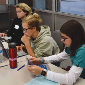 Eighth grader Ryan Younger (left), seventh grader Chloe Pithie (center), and sixth grader Taylor Waimrin (right), all from Immaculate Heart Middle School, work together to design a prototype of their app. (photo courtesy of Immaculate Heart)
