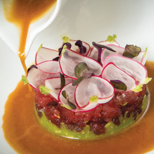 The tuna tartare is cut in spirals, giving the dish a texture more similar to sashimi, yet easier to eat with chopsticks. The creamy avocado base with a ginger lime sauce provides a savory, salty and zesty finish. (photo courtesy of Waldorf Astoria Beverly Hills)
