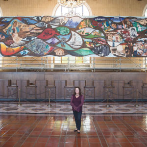 """Artist Barbara Carrasco stands in front of """"L.A. History: A Mexican Perspective"""" at Union Station. (photo by Sean Meredith)"""