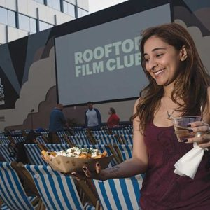 Filmgoers can enjoy food and drinks under the stars during Rooftop Cinema Club's film screenings. (photo courtesy of Rooftop Cinema Club)