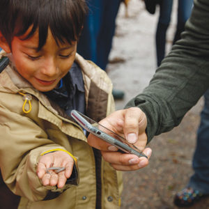 A participant in a NHMLA nature walk at Augustus F. Hawkins Nature Park in South L.A. holds a discovery to submit via iNaturalist. (photo courtesy of Natural History Museum of Los Angeles County)