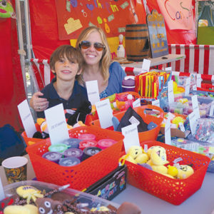 This Rosewood parent had a special helper at one of the booths at last year's fair. (photo courtesy of Linda Crowder/Rosewood Avenue Elementary)