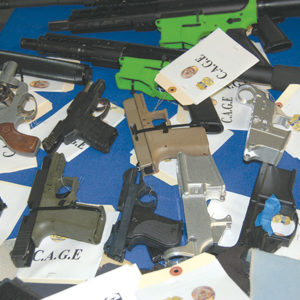 Numerous guns in various stages of assembly that were confiscated by law enforcement were displayed during a press conference announcing the arrests of 10 individuals accused of felony firearms violations.