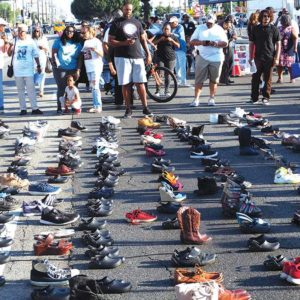 Local residents brought shoes and placed them in the street near the intersection of Vermont and Manchester avenues to represent victims of gun violence. (photo by Luke Harold)