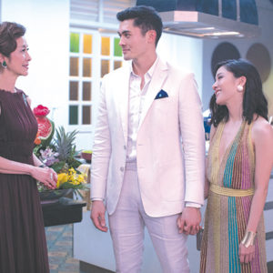 """Michelle Yeoh (left) stars as Eleanor Sung-Young, Henry Golding appears as Nick Young and Constance Wu portrays Rachel Chu in """"Crazy Rich Asians,"""" a heartwarming movie that deviates from conventional rom-com storylines. (photo courtesy of Warner Bros. Pictures)"""