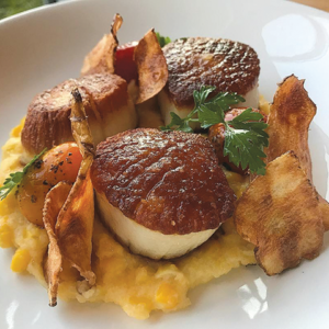 Seared diver scallops on a bed of sweet  corn polenta and fired sunchokes. (photo courtesy of Commerson)