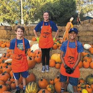 St. Brendan School eighth graders Oliver Tostado (left), Kaya Gips and Theo Collins are volunteers at Wilshire Rotary's pumpkin patch on Larchmont Boulevard. (photo courtesy of Wendy Clifford/Wilshire Rotary)