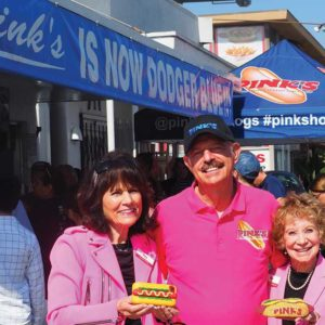 Gloria, left, Richard and Beverly Pink cheered on their favorite team, the Los Angeles Dodgers, by turning Pink's blue. A hungry Manny Machado fan waits in line for his Blue's bacon chili cheese hot dog. (photo by Luke Harold)
