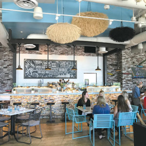The decor inside Herringbone Santa Monica offers pleasing marine blue and green colors with whimsical art. Lower left, tuna poke, chilaquiles and salmon Benedict are popular brunch offerings. (photos by Jill Weinlein)