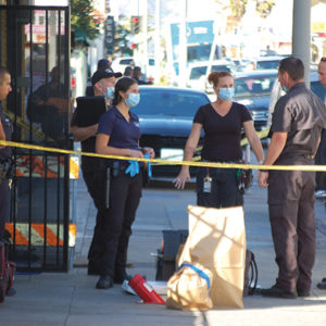 Coroner's office employees consulted with LAPD investigators outside a marijuana dispensary on Western Avenue where two people were shot and killed on Nov. 12. The homicides remain under investigation. (photo by Edwin Folven)