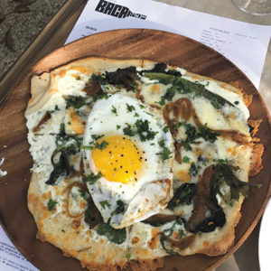 The brunch egg pizza at Bacari W. Third pairs well with a bottomless mimosa. (photo by Jill Weinlein)