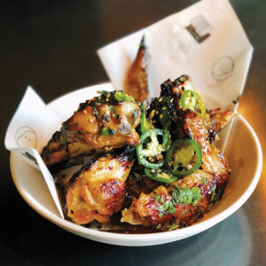 Robata-grilled chicken wings with ume-boshi, green chili, mint and sansho have a nice kick to them. (photo courtesy of Inko Nito)